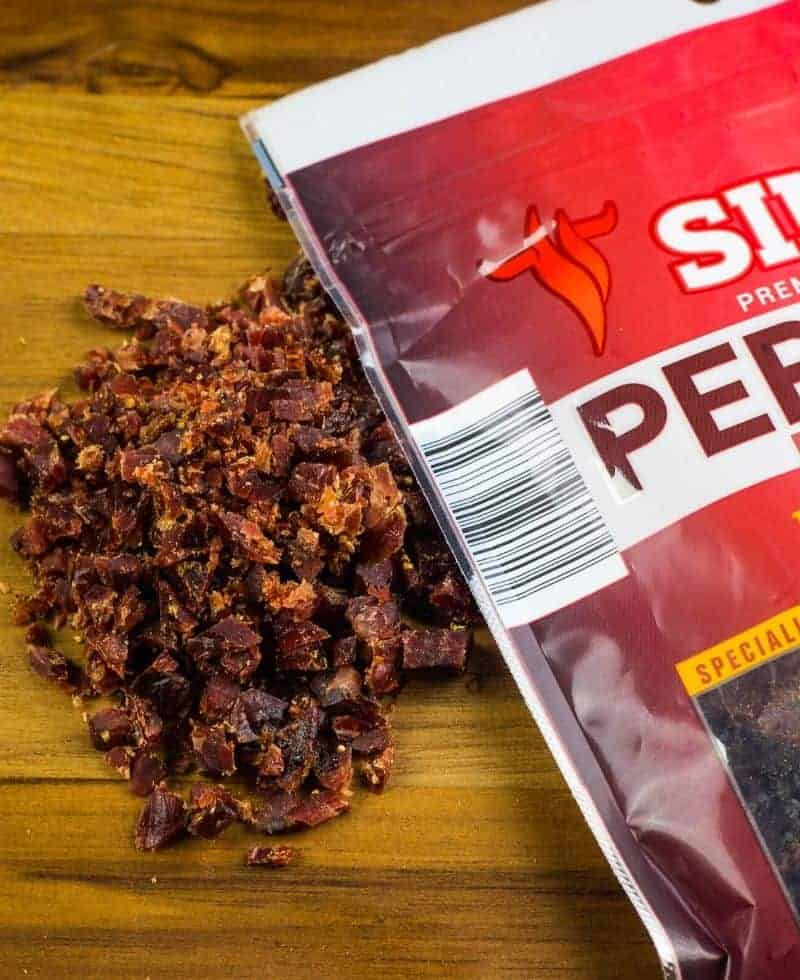 chopped beef jerky next to the bag of simms beef jerky on a wooden cutting board