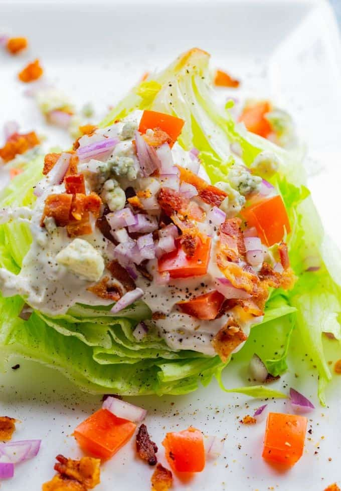 classic iceberg lettuce topped with homemade blue cheese dressing, bacon, and tomatoes on a white plate