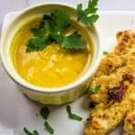 homemade honey mustard sauce with fresh parsley in a yellow bowl.