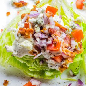 A classic wedge salad loaded with bacon. tomatoes, onion, and fresh blue cheese.
