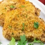 Crispy pork chops with a bread crumb coating on a white plate