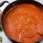 a large grey saucepan filled with tomato sauce topped with chopped parsley