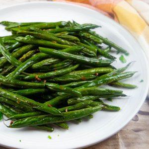 fresh oven roasted green beans on a white platter
