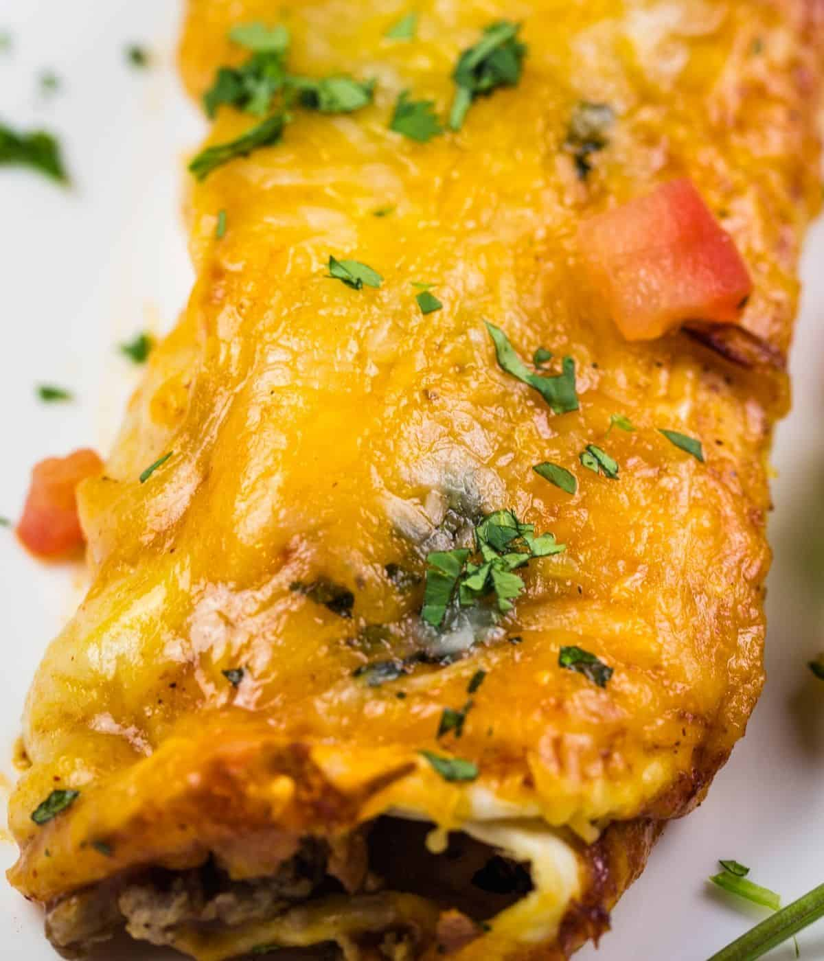 Cheesy beef enchilada topped with cheese, tomatoes, and fresh cilantro