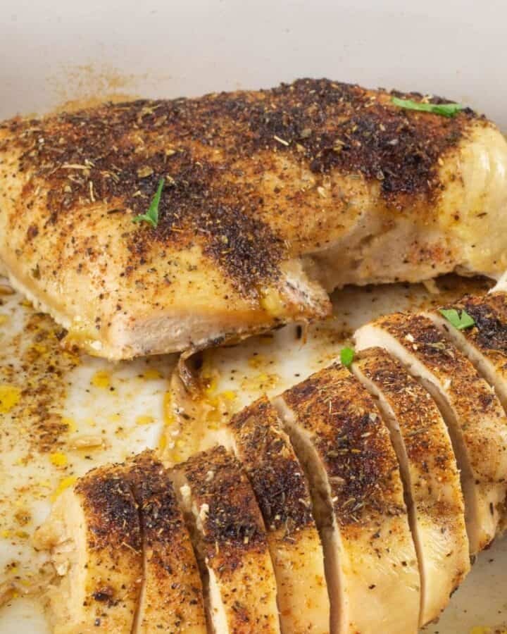 Sliced baked chicken in a baking pan