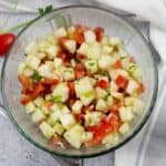 large bowl of diced cucumber and tomatoes with a vinaigrette