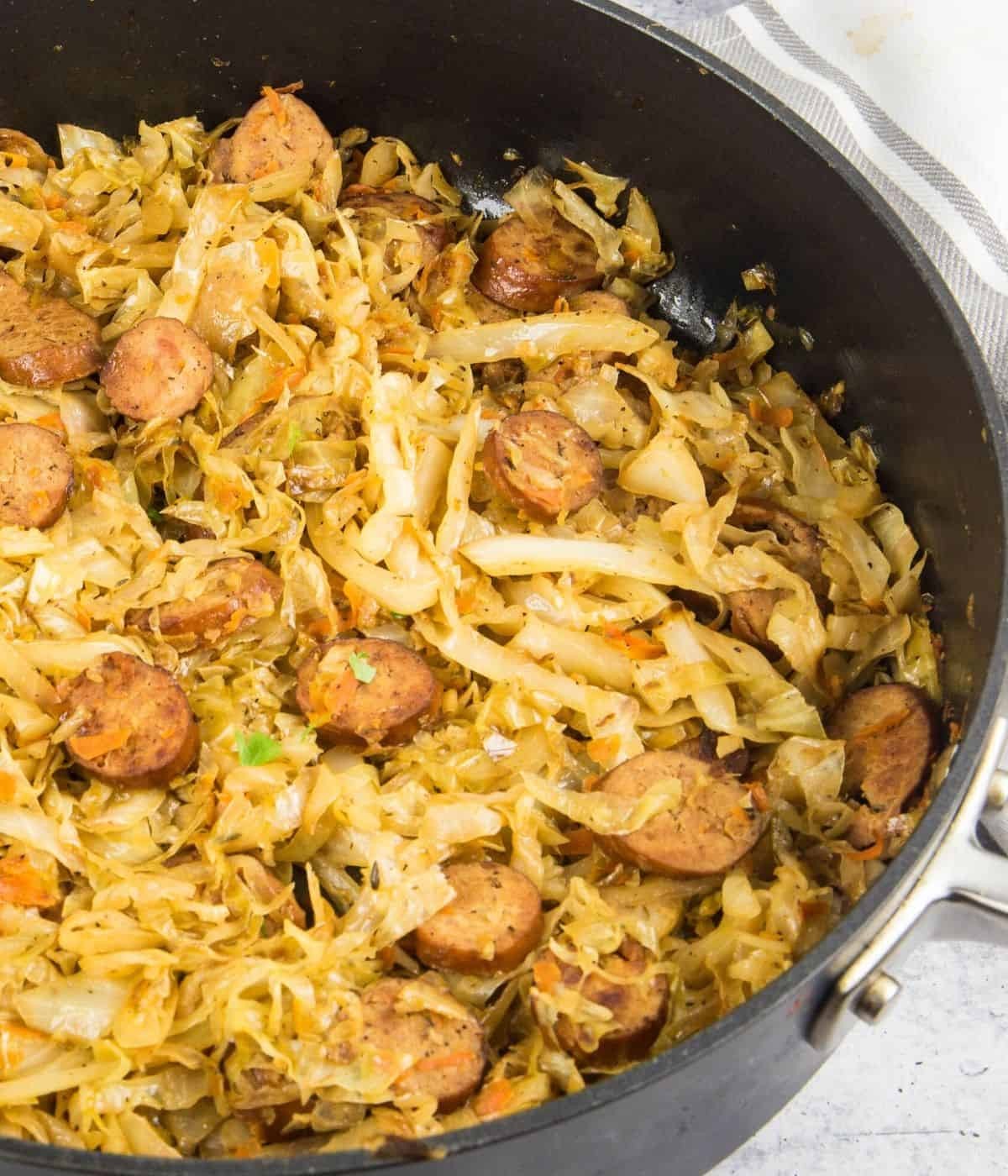 A large skillet with shredded cabbage and smoked sausage.
