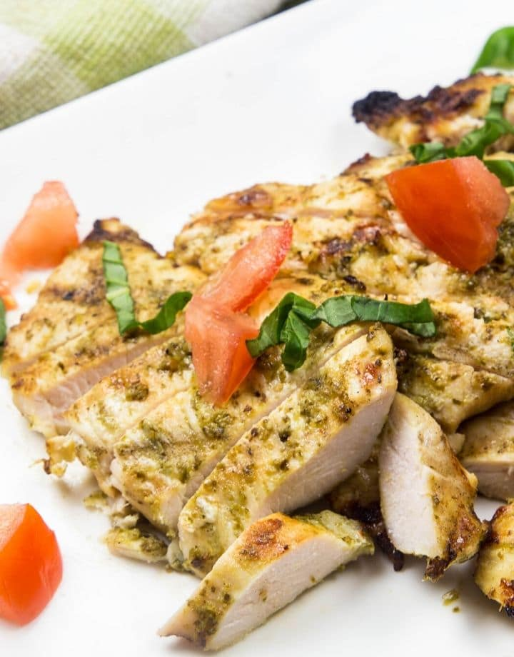 A large white plate with grilled chicken in a homemade pesto sauce