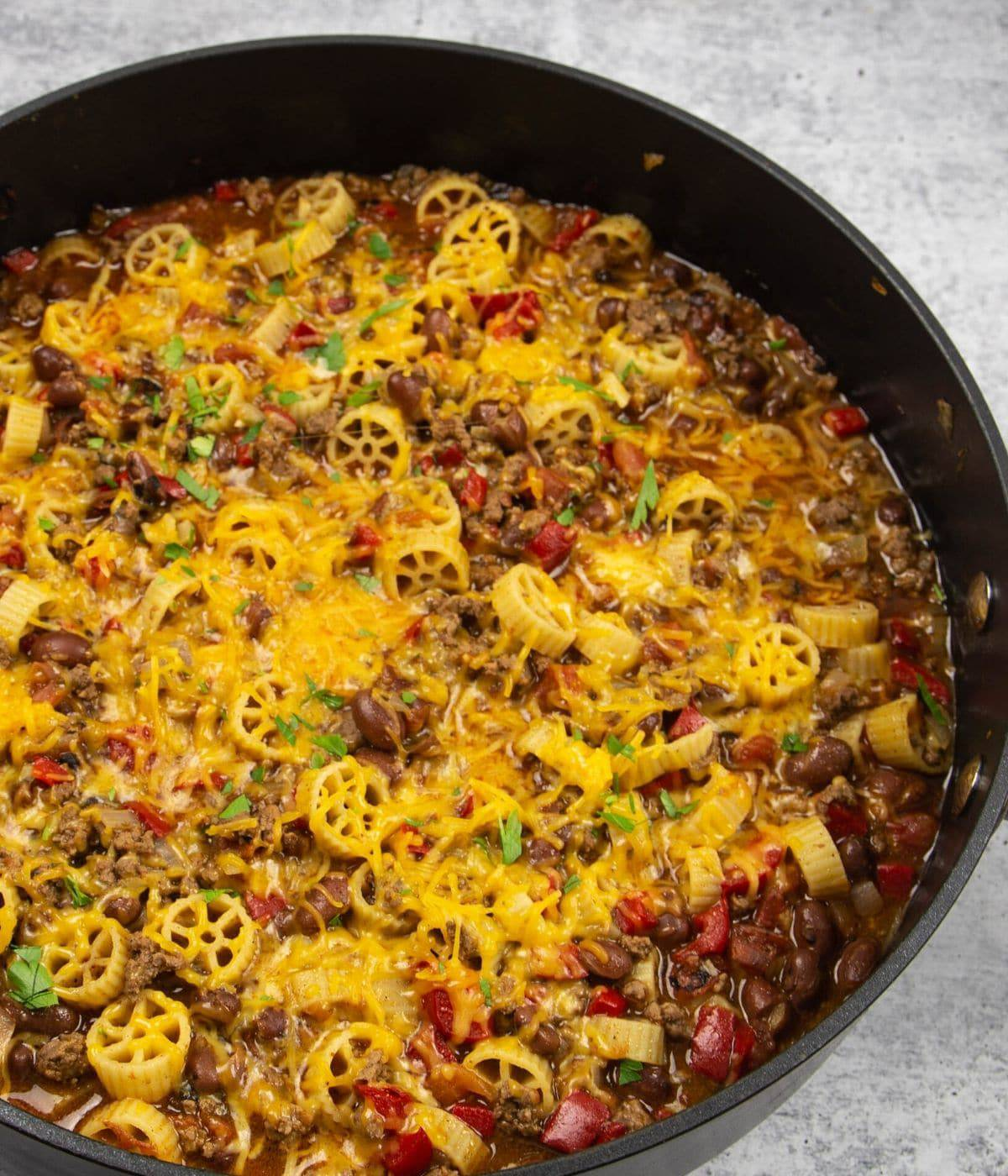A large black skillet with pasta and ground beef topped with melted cheese.