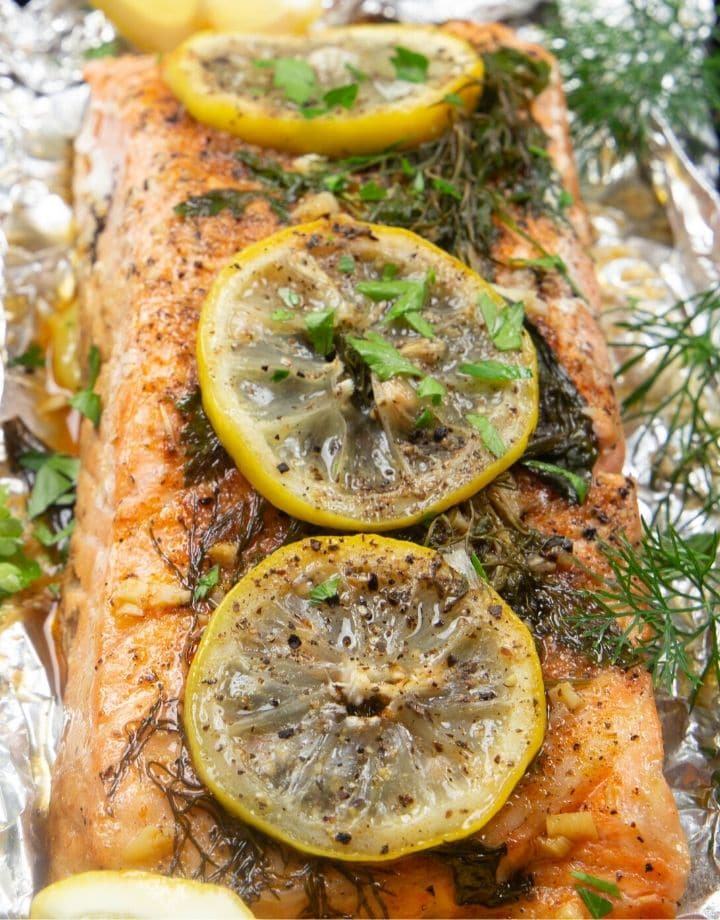 Cooked salmon topped with dill and lemon on a large piece of aluminum foil.