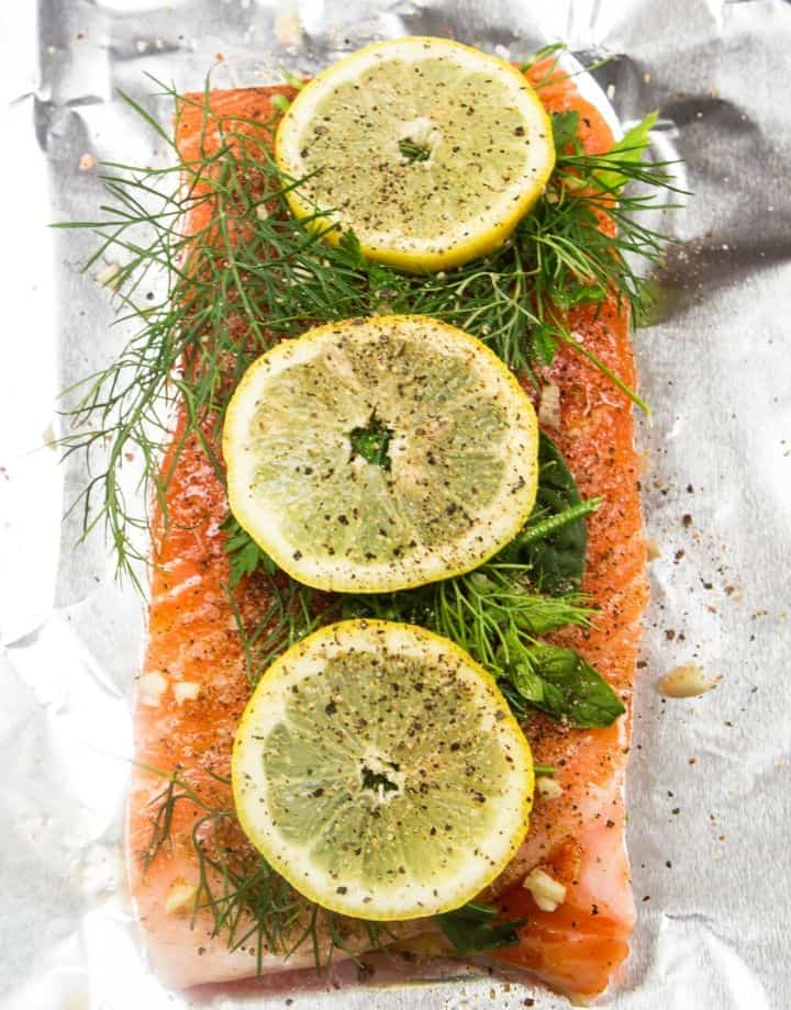 raw salmon fillet topped with fresh dill and lemon on foil ready to go in the oven