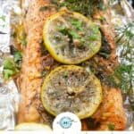 salmon on foil that has been grilled and topped with lemon and herbs