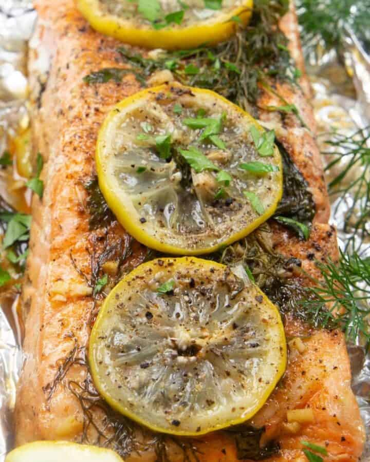 Grilled salmon topped with lemon and herbs, wrapped in foil and grilled.