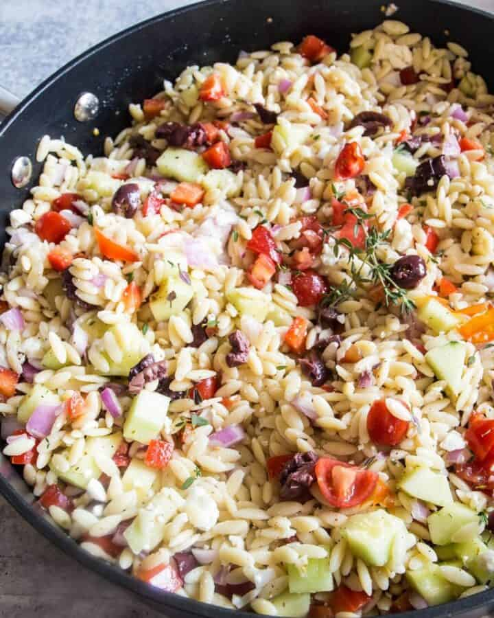 A large black pan holding orzo salad