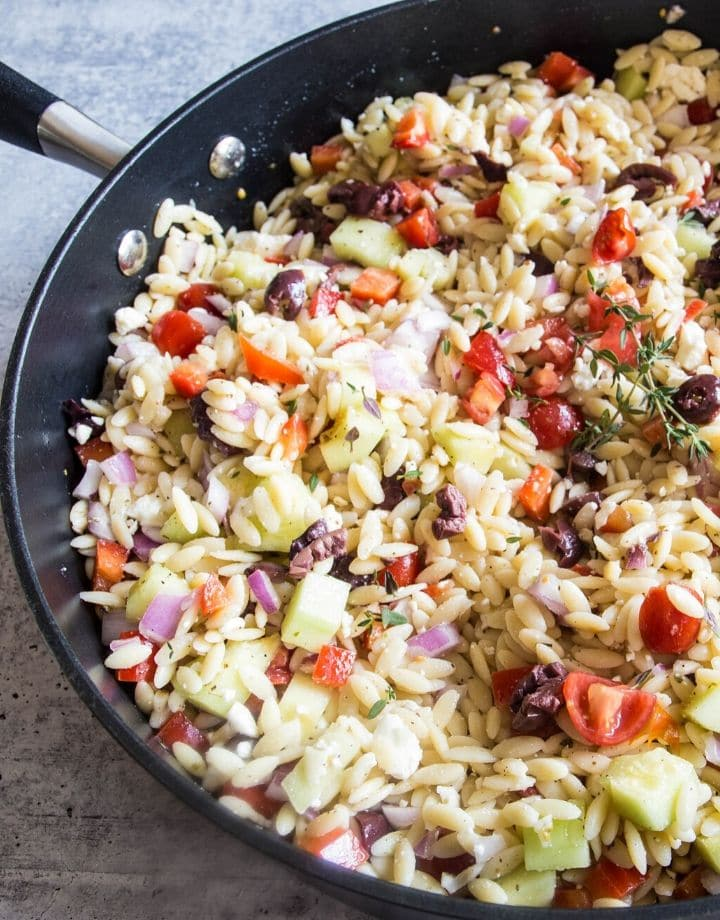 A top view or greek orzo salad filled with veggies