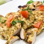 Sliced boneless chicken breasts coated with basil pesto on a white plate, topped with chopped fresh basil and tomato.