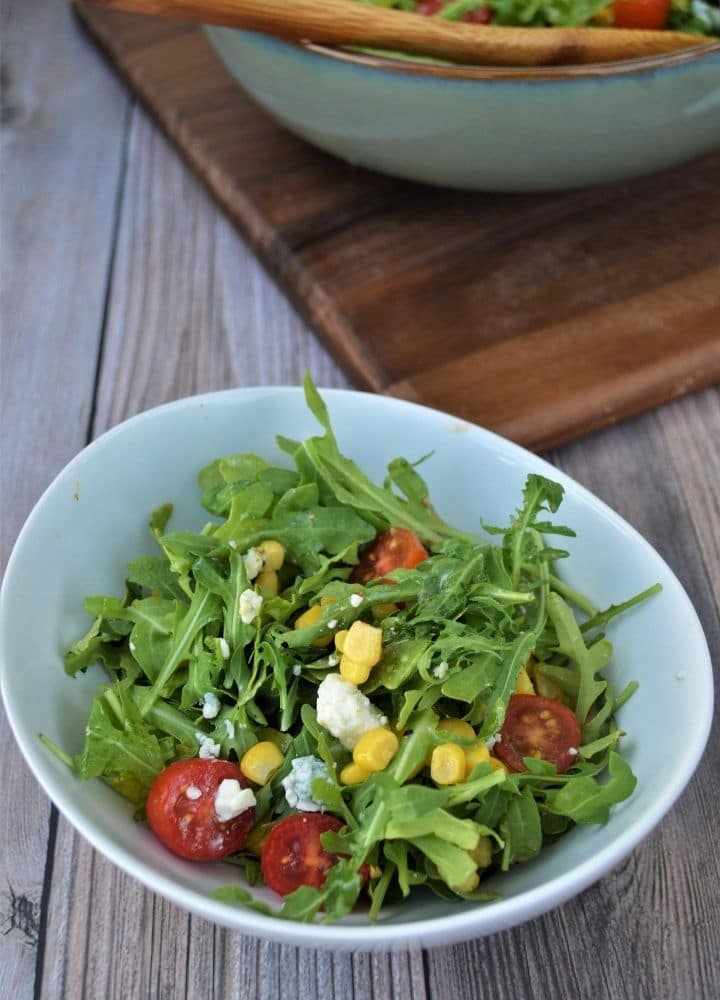 A white bowl with peppery arugula salad, tomatoes, and corn.