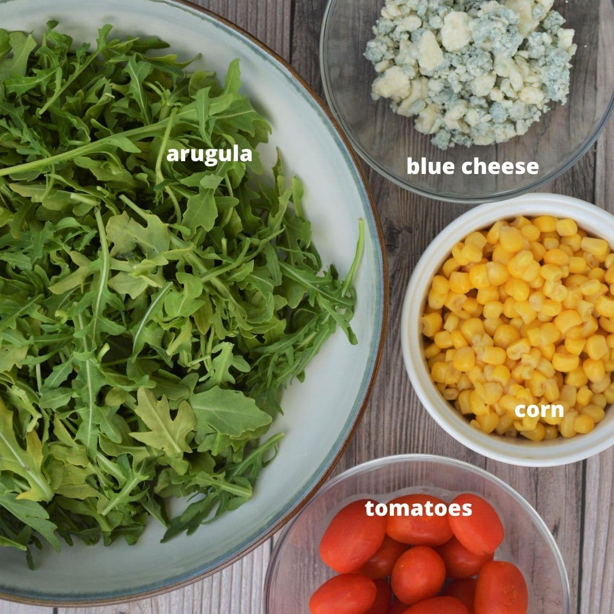 the ingredients for a salad, arugula, blue cheese crumbles, corn, and tomatoes.