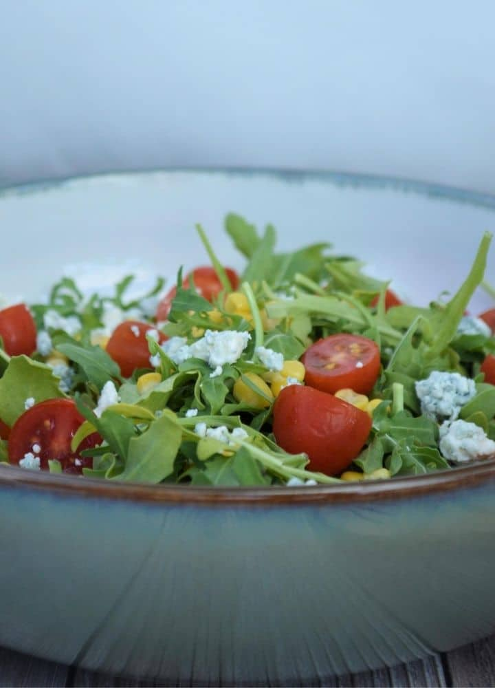 A white bowl with a brown trim filled with salad topped with blue cheese, corn, and tomatoes.