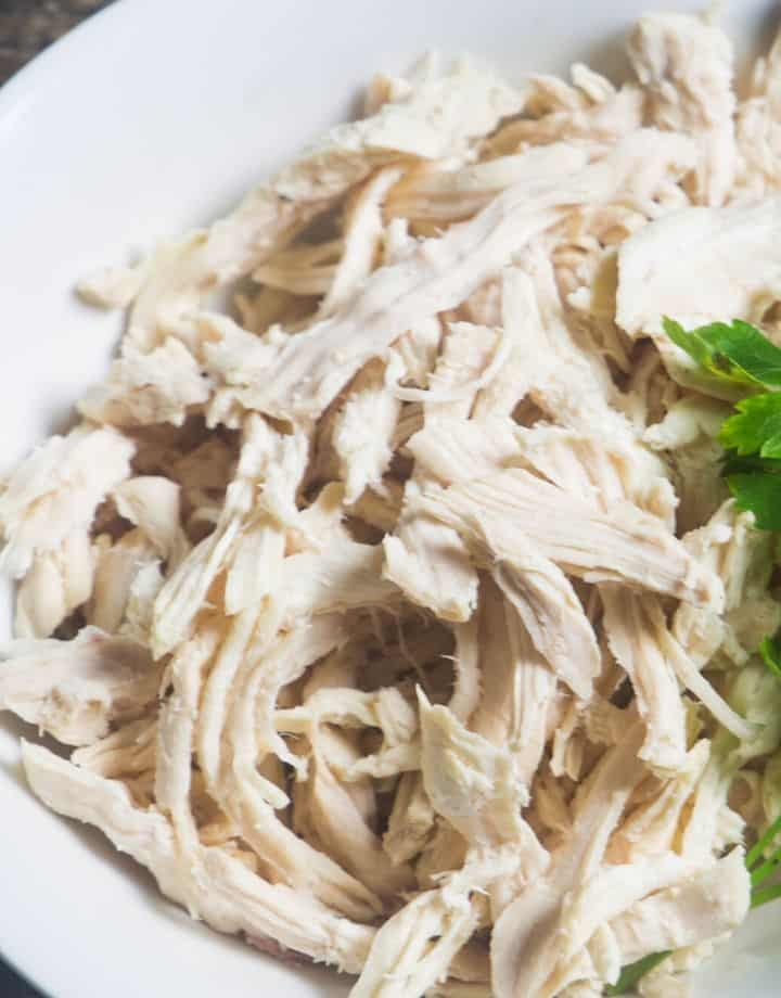 Cooked chicken made in the instant pot and shredded in a white bowl.