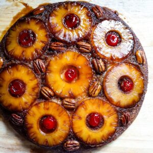 An overhead view of a pineapple upside down cake topped with pineapple slices, pecans, and maraschino cherries.