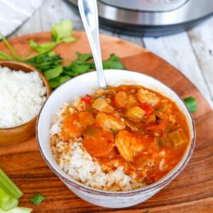 A bowl of rice topped with Creole style gumbo with a spoon in the bow.
