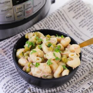 A black bowl with spiral pasta, peas, and tuna on a linen napkin.