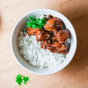 A bowl of white rice topped with Korean BBQ chicken and white sesame seeds
