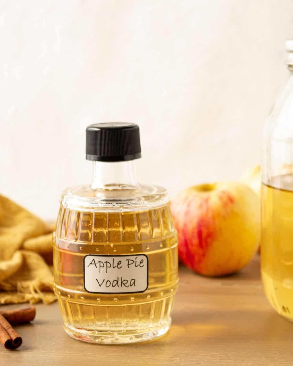 A homemade bottle of apple pie vodka with fresh apples and cinnamon on the side.