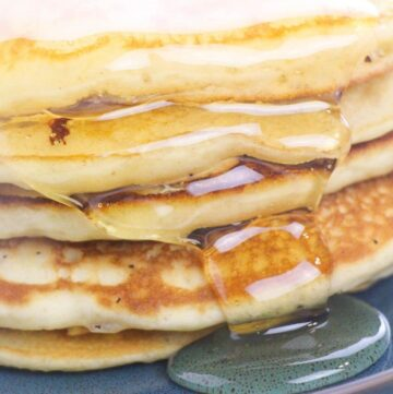 A stack of fluffy buttermilk pancakes dripping with maple syrup.