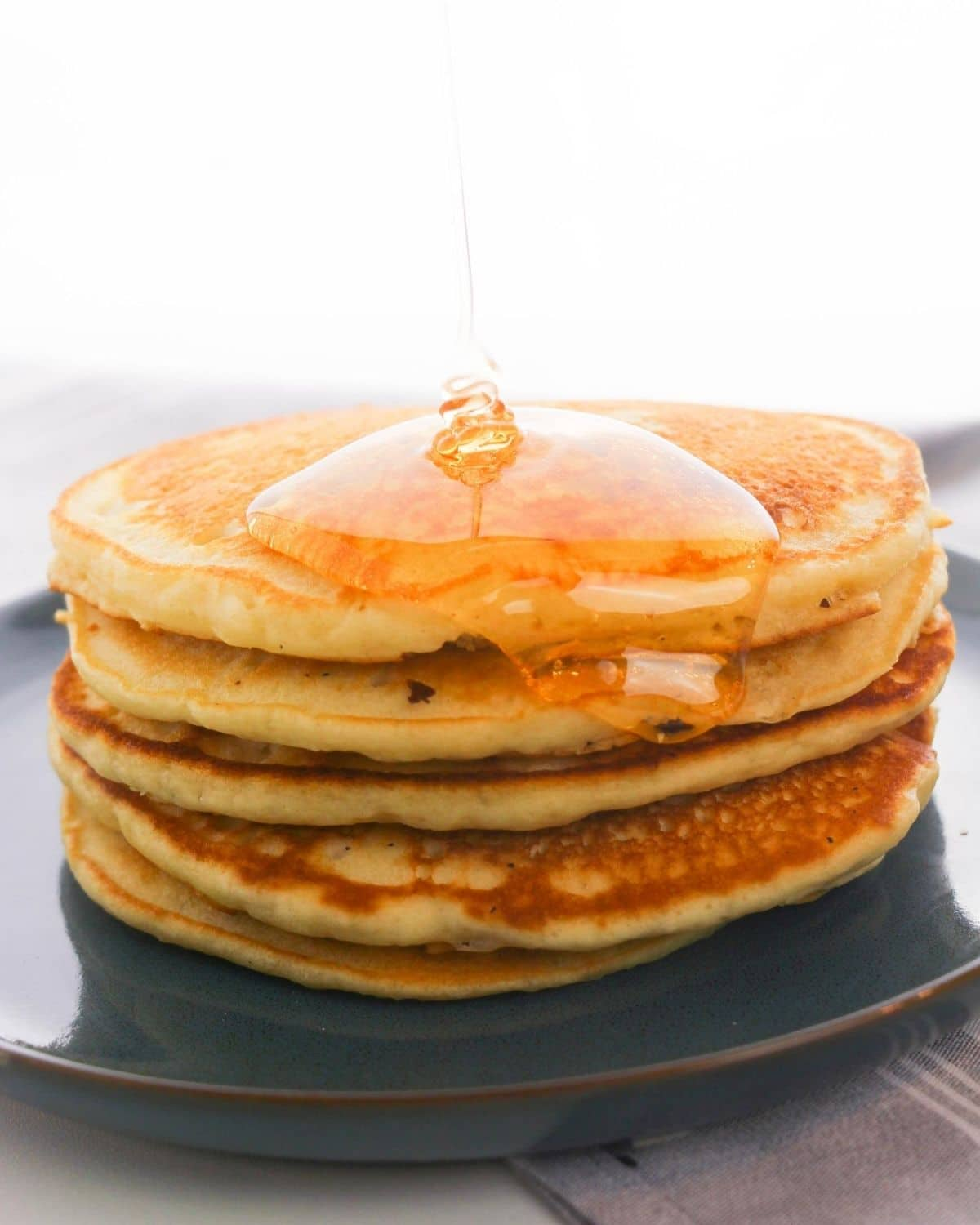 A stack of pancakes with maple syrup being poured over them.
