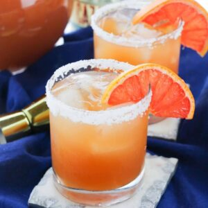 A clear glass filled with grapefruit margarita with salt rimming the glass.