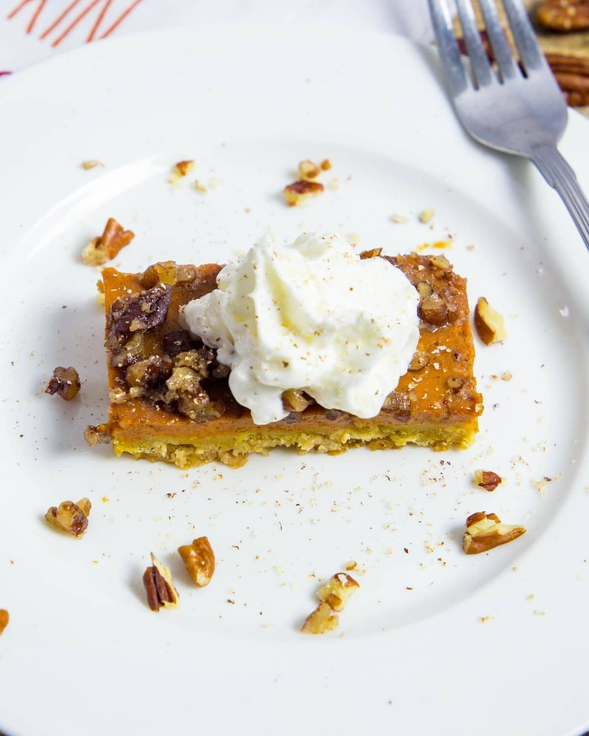 A white plate with a rectangle slice of pumpkin pie bars topped with whipped cream.