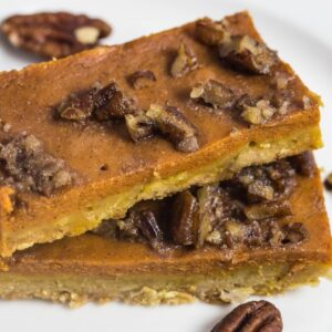 Pumpkin pie bar topped with candy pecans on a white plate