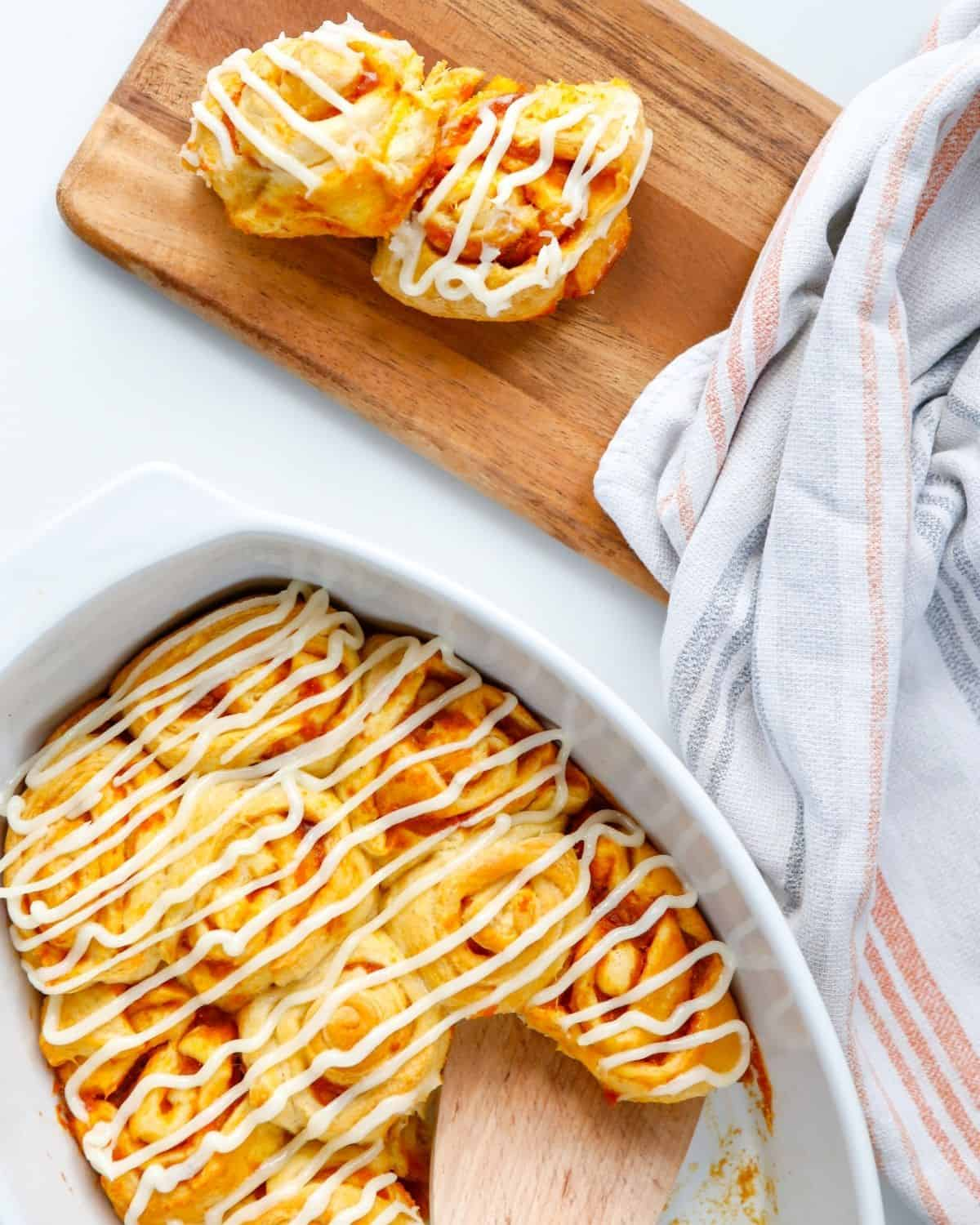 Pumpkin pie cinnamon rolls in a white dish and a side tray with two buns on the platter