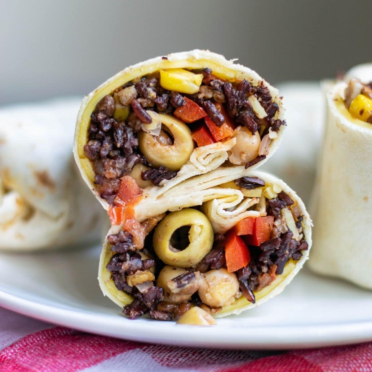 A veggie wrap filled with black rice, olives, tomatoes, and corn.