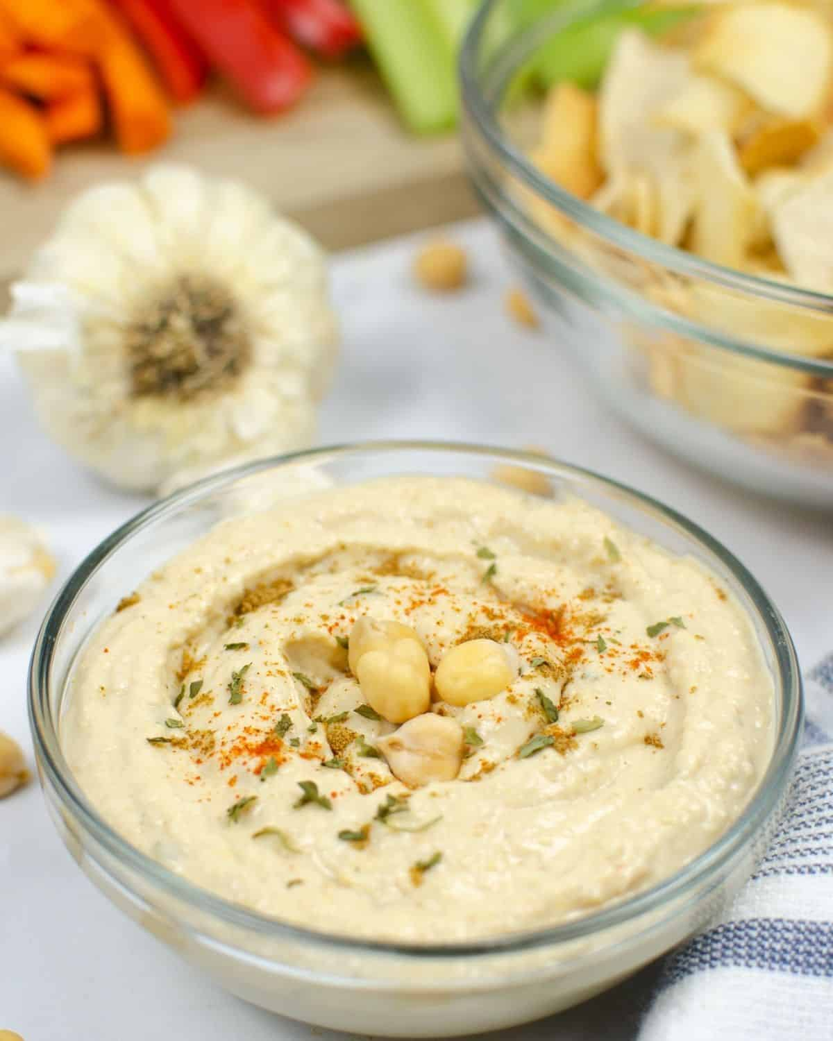 A bowl of hummus topped with chickpeas, paprika and oil