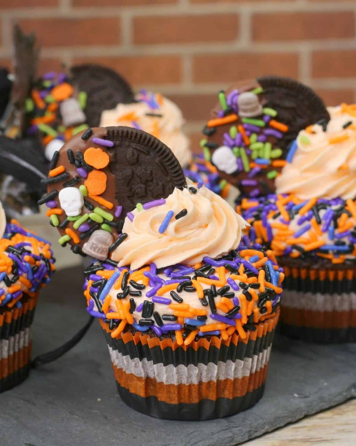 Halloween cupcakes decorated with festive oreos and icing with sprinkles.