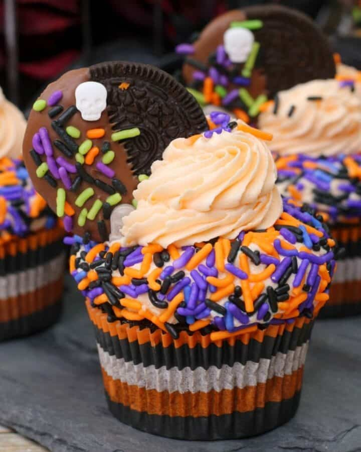 Cupcakes with a halloween theme with orange and purple sprinkles.