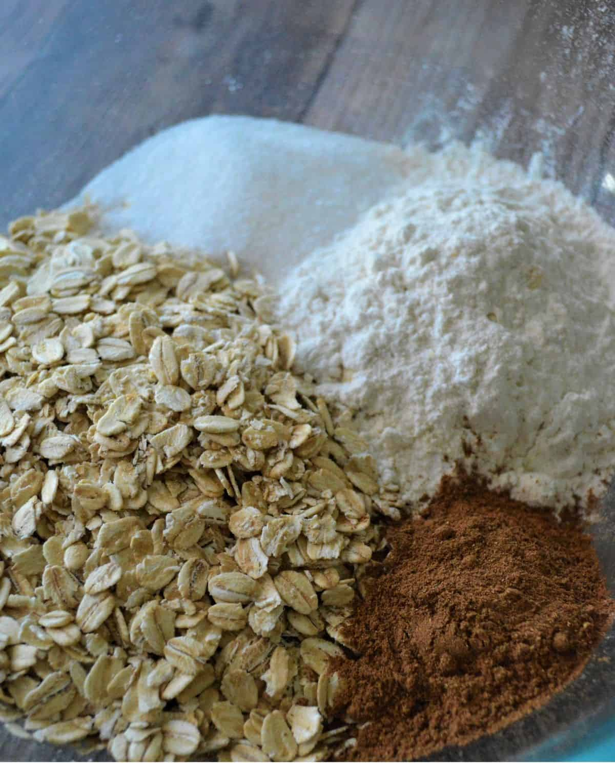 The dry ingredients of flour, oats, pumpkin pie spice, sugar, and salt to make oat bars.