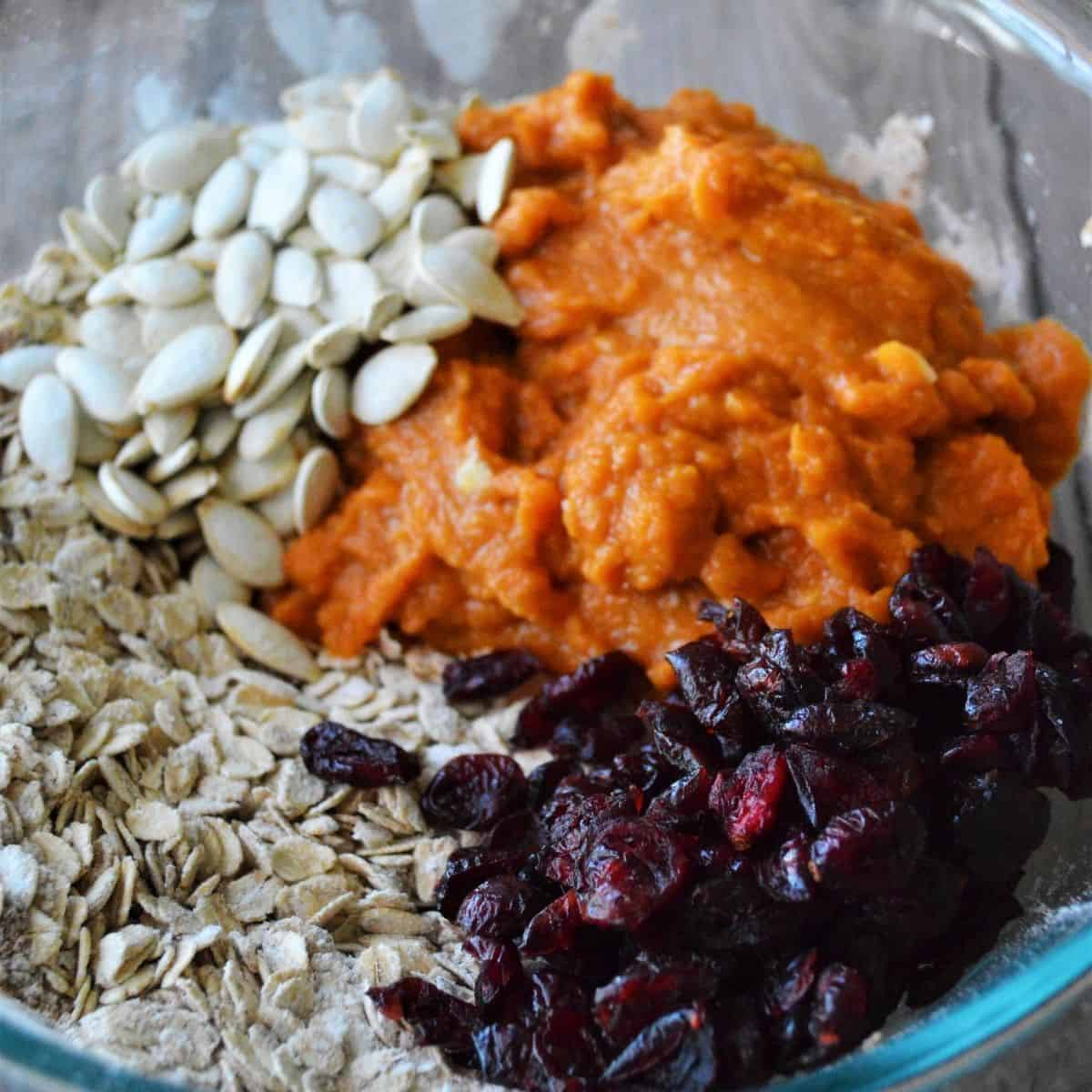 Combining the wet and dry ingredients plus pumpkin seeds and dried cranberries