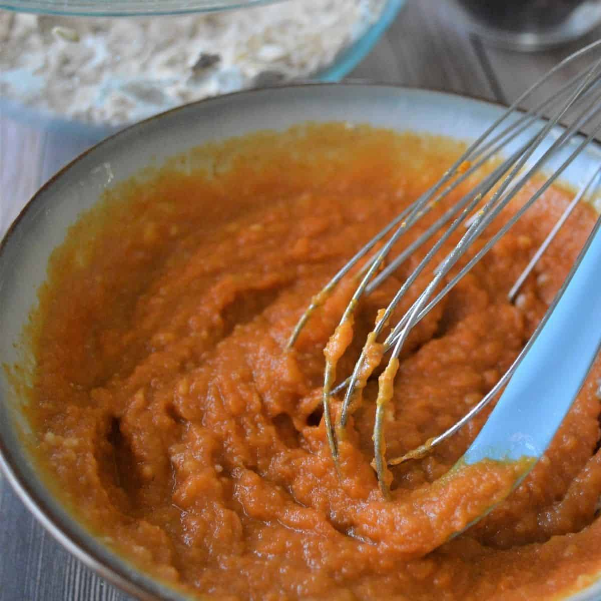 Pumpkin puree mixed to be added to the dry ingredients to make pumpkin cranberry oat bars.