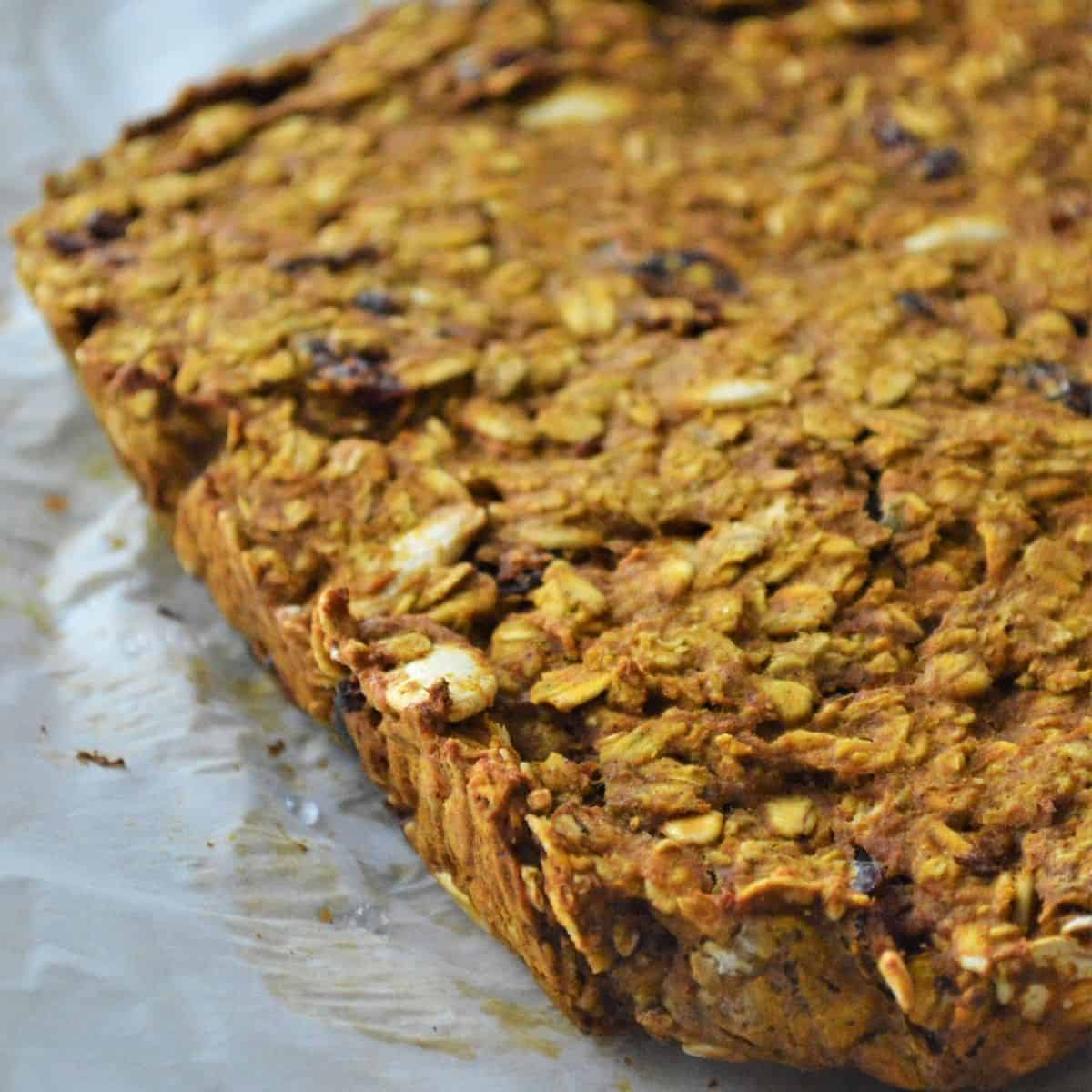 Oat bars on parchment paper waiting to be cut into serving pieces.