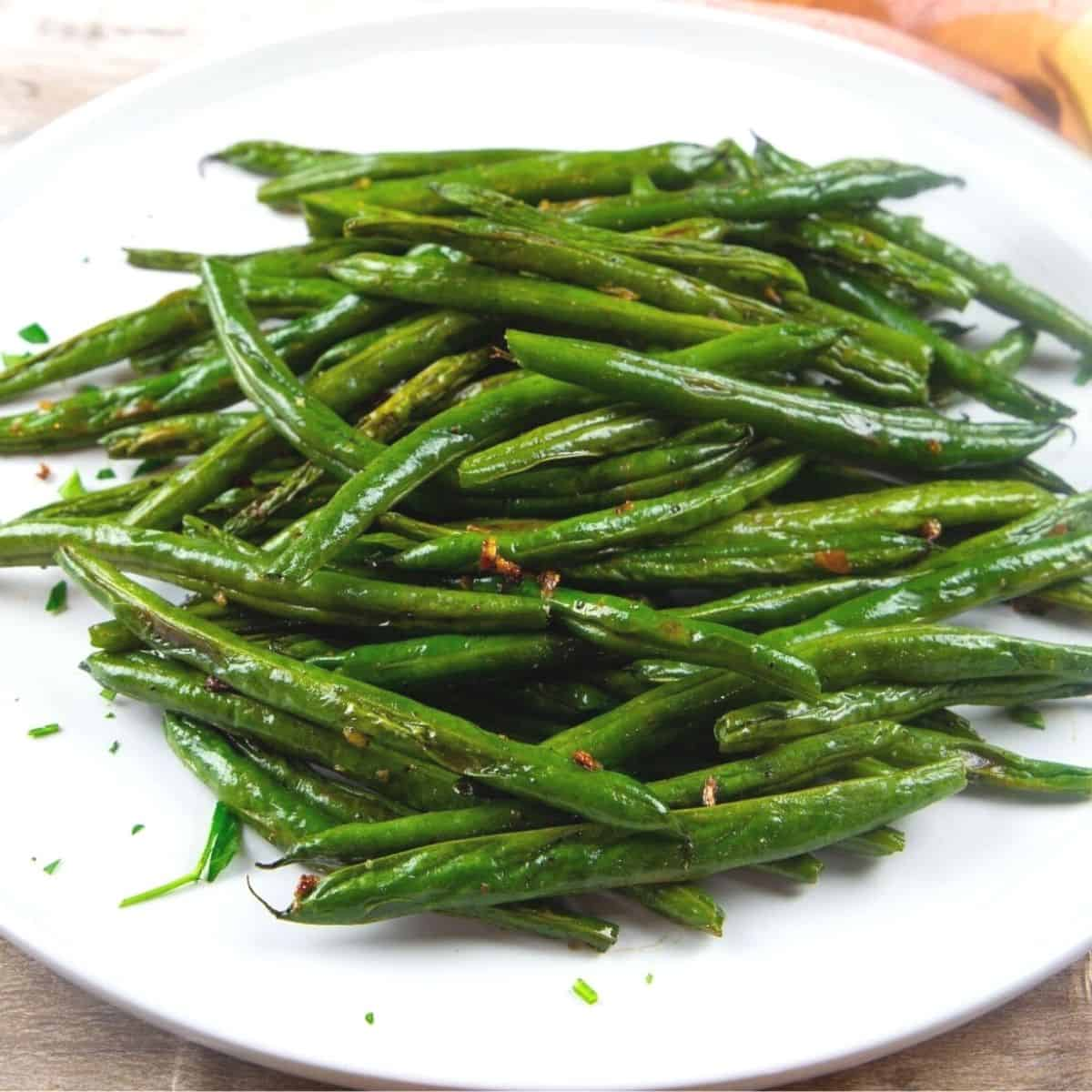 A white plate loaded with green beans that have been roasted.