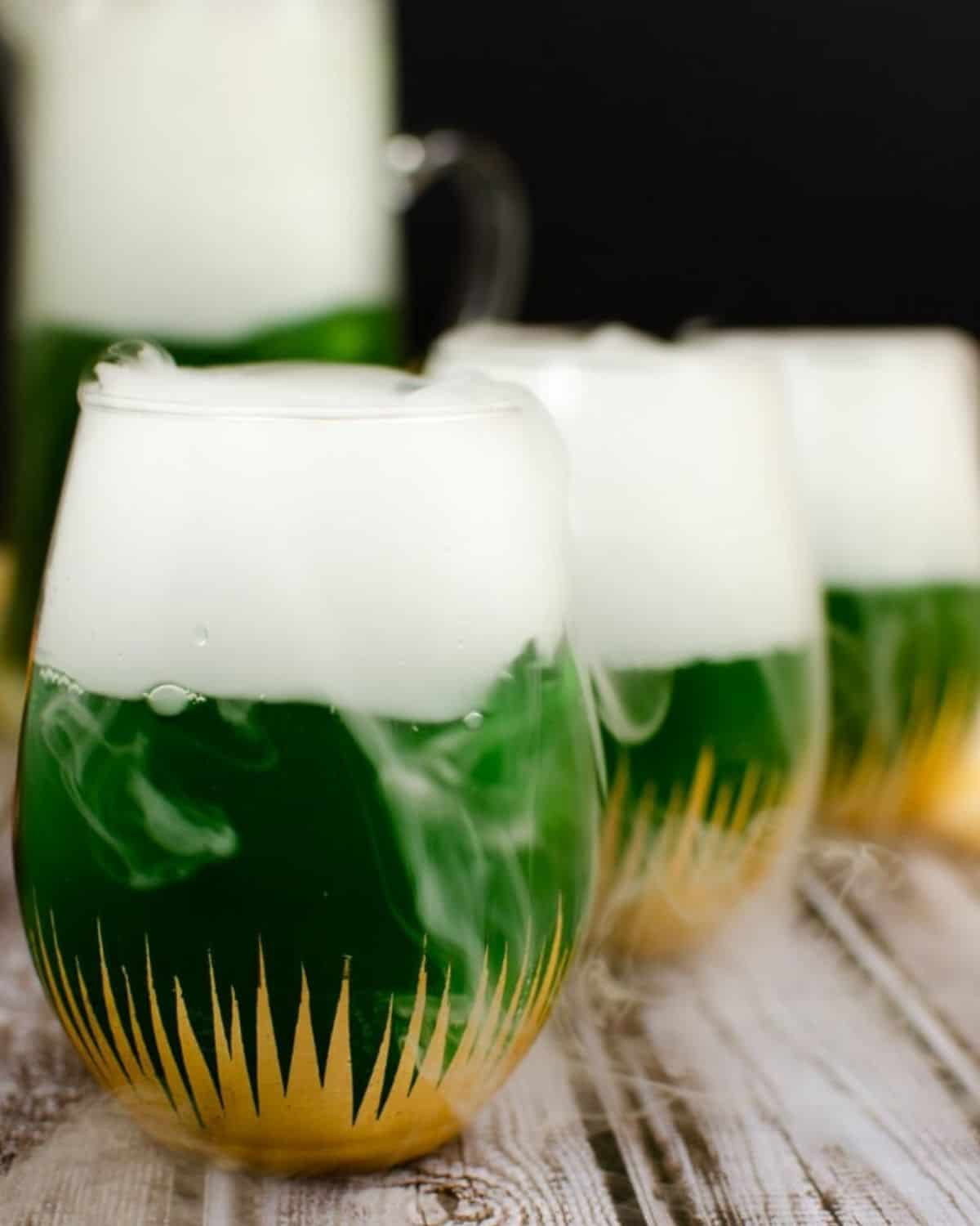A festive green cocktail for Halloween with smoking dry ice coming out of the glass