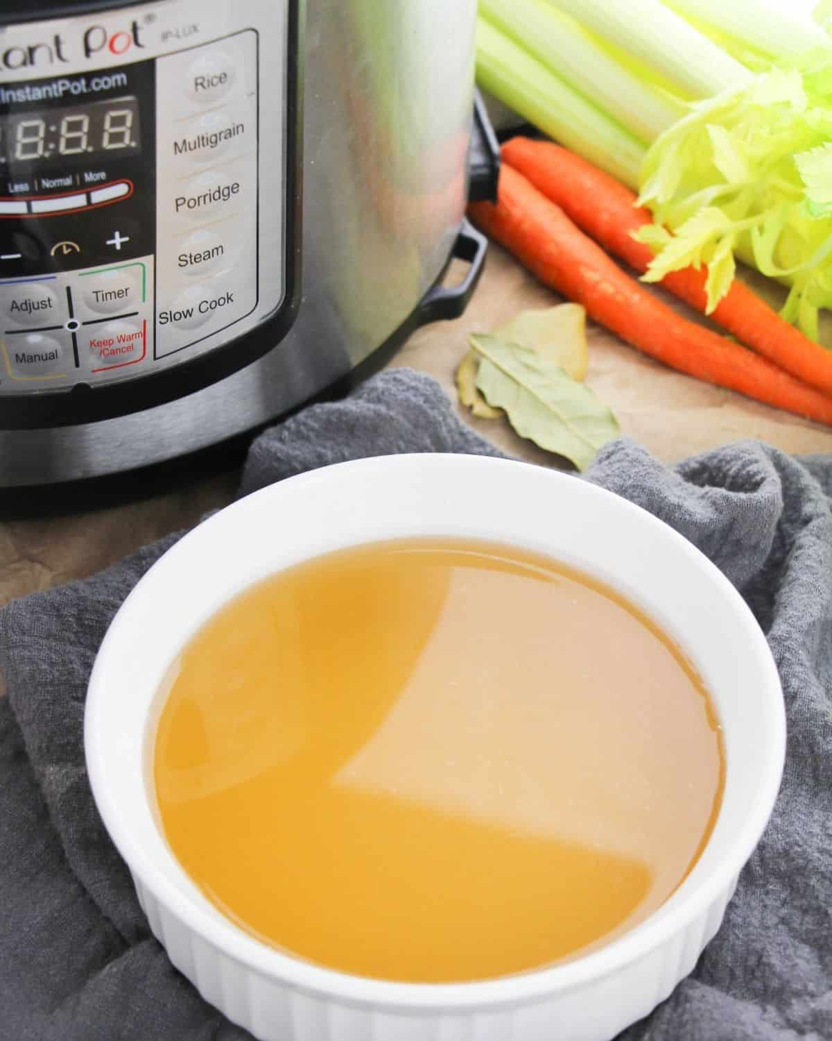 turkey stock made in the pressure cooker in a bowl surrounded by veggies and an Instant Pot.