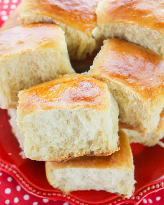 A few Hawaiian sweet rolls stacked on a platter.