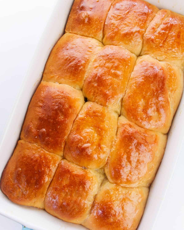 Baked Hawaiian sweet rolls in a white baking pan