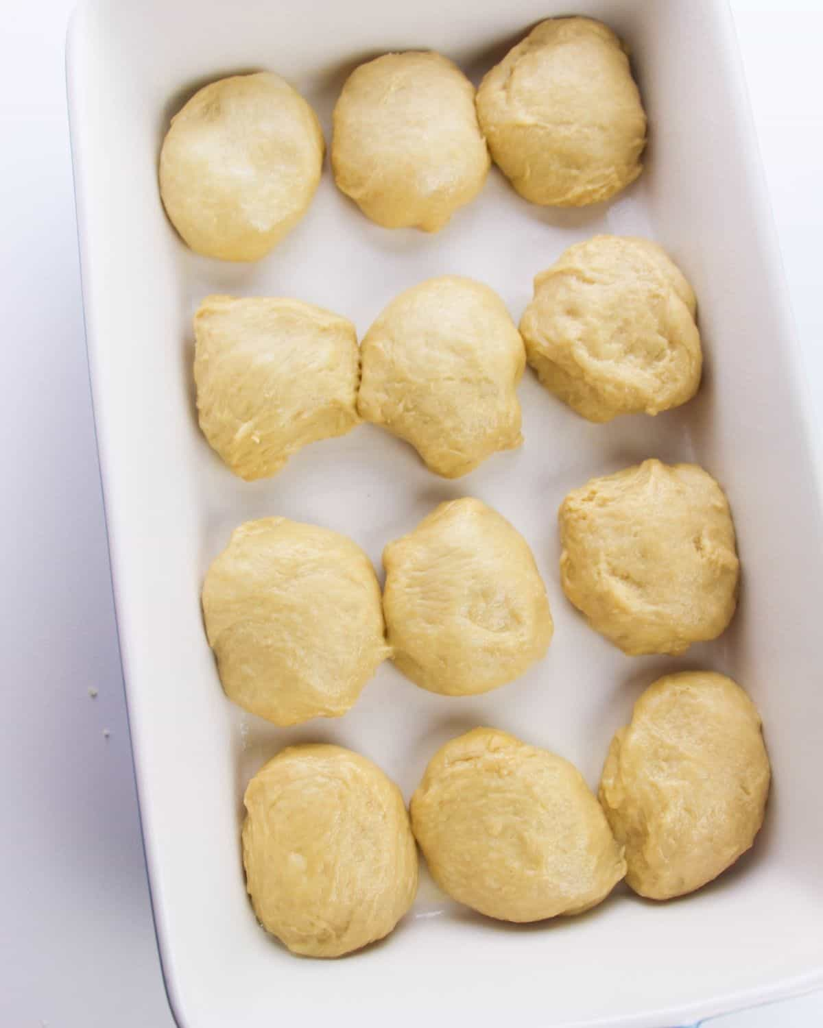 Unbaked rolls in a white baking dish to proof and double in size.