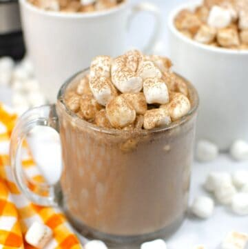 hot chocolate in a clear mug topped with marshmallows